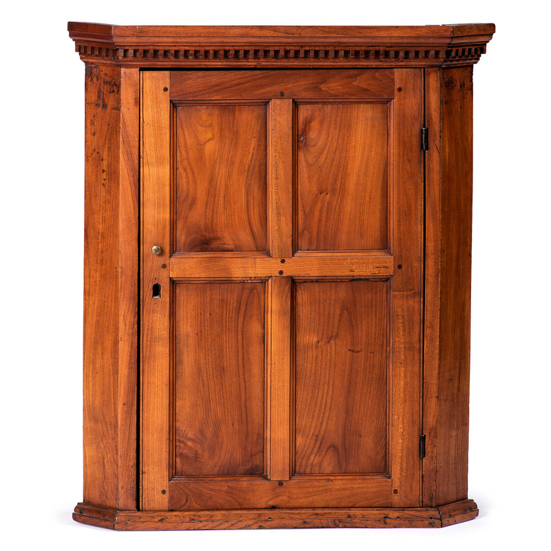 A Dentil Molded and Paneled Hanging Corner Cupboard in Cherry