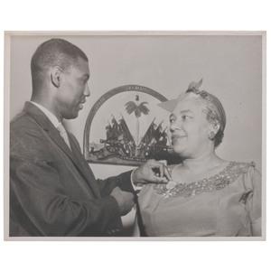 DUNNIGAN, Alice (1906-1983). Press photograph of Dunnigan receiving the 'Award of Merit' from Haitian Ambassador Fern D. Baguidy, Sr. [Washington, DC], [ca 1959].